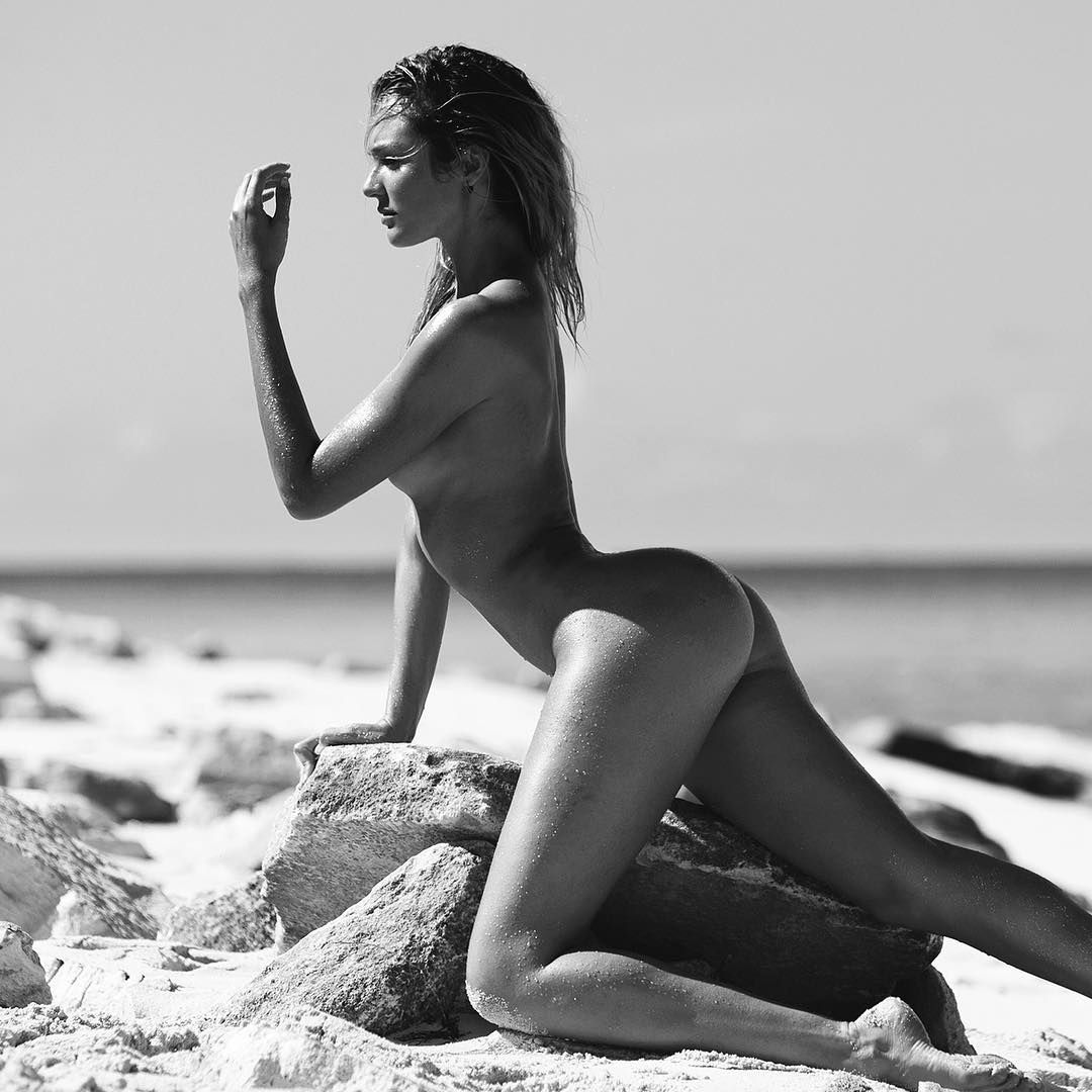 Candice Swanepoel totally naked on a rock by the ocean