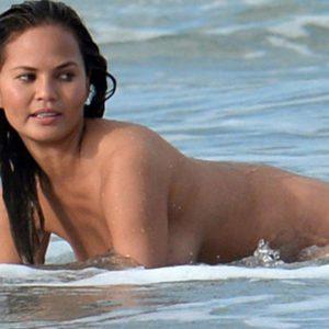 Chrissy Teigen naked in the ocean on all fours