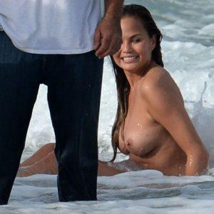 Chrissy Teigen topless in an ocean wave