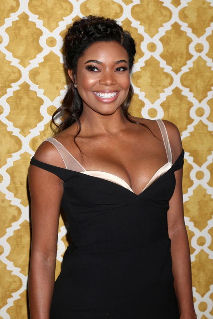 Gabrielle Union in a black dress smiling wide