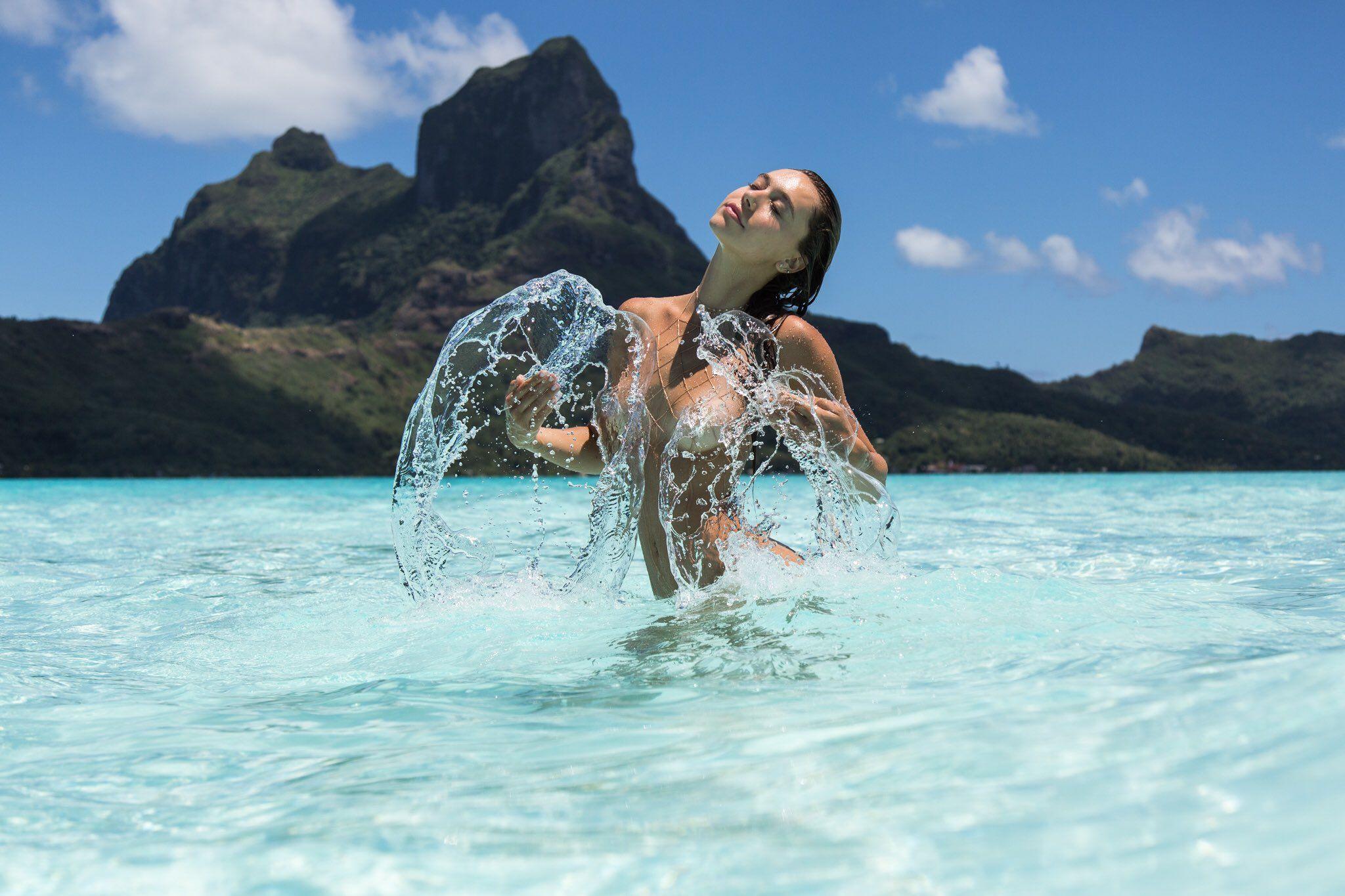 Alexis Ren in water with no top