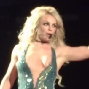 While singing Britney Spears boob pops out of her green dress