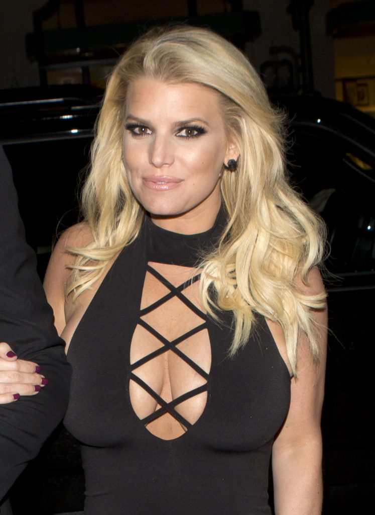 Jessica Simpson wearing black low deep v dress and smiling for the camera