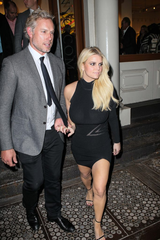 Jessica Simpson in a tight black dress showing off her toned legs while she holds hands with her husband