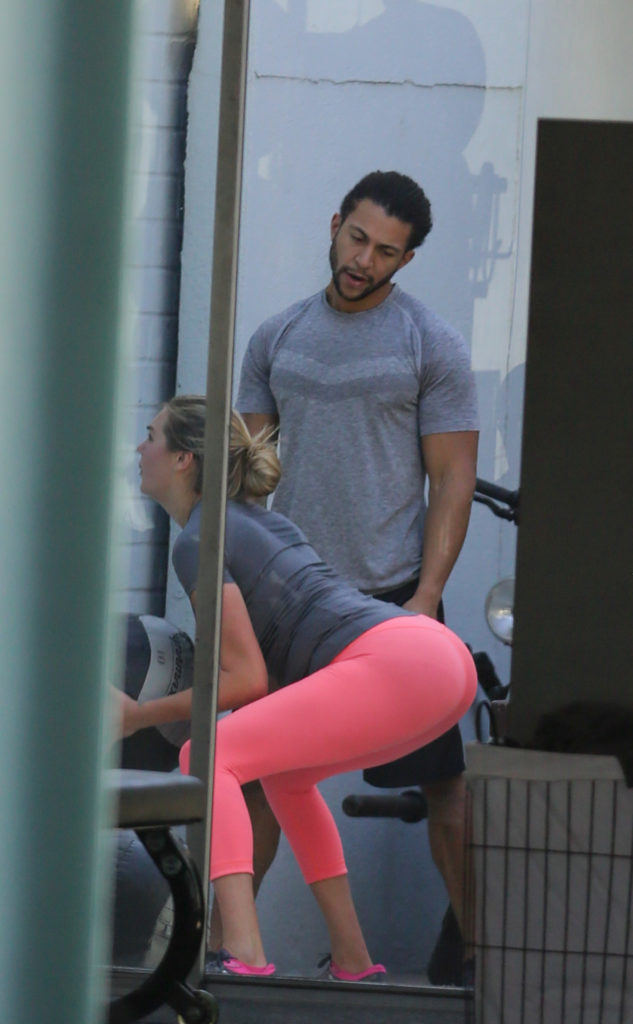 Kate Upton in bright pink yoga pants squatting