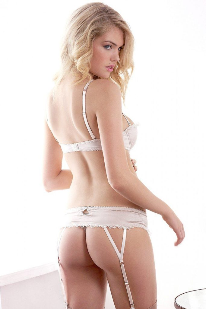Kate Upton in sexy cream lingerie showing off her ass and looking sideways