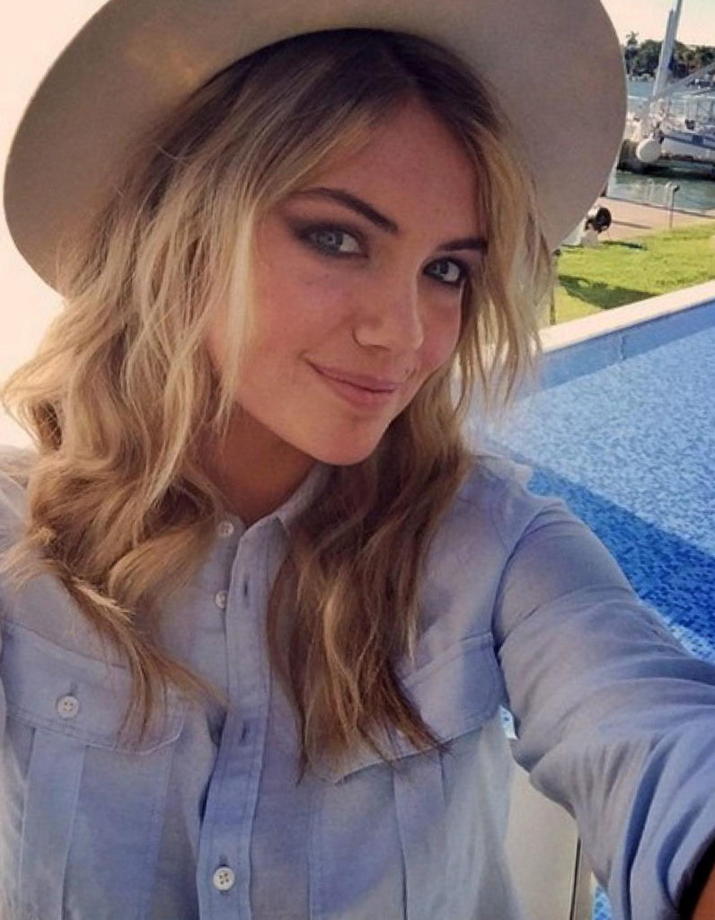 Kate Upton in a tan hat next to a swimming pool taking a selfie