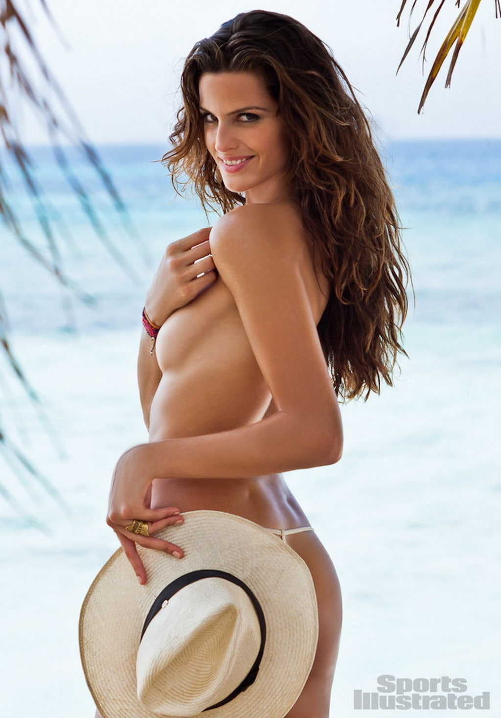Izabel Goulart topless with a hat on the beach